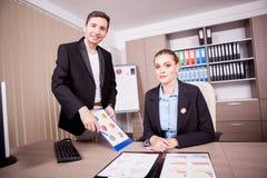 Επιχειρηματίας και επιχειρηματίας στην αρχή με τα διαγράμματα στον πίνακα Στοκ φωτογραφία με δικαίωμα ελεύθερης χρήσης