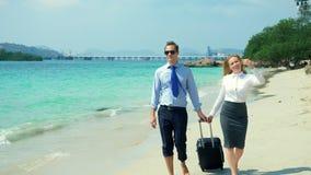 Επιχειρηματίας και επιχειρησιακή γυναίκα με μια βαλίτσα που περπατά κατά μήκος της άσπρης παραλίας άμμου στο νησί απόθεμα βίντεο