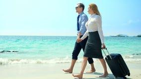 Επιχειρηματίας και επιχειρησιακή γυναίκα με μια βαλίτσα που περπατά κατά μήκος της άσπρης παραλίας άμμου στο νησί στοκ εικόνες