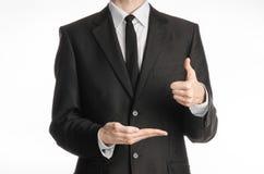 Επιχειρηματίας και θέμα χειρονομίας: ένα άτομο σε ένα μαύρους κοστούμι και έναν δεσμό με το αριστερό χέρι του παρουσιάζει ότι οι  Στοκ φωτογραφία με δικαίωμα ελεύθερης χρήσης