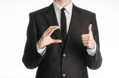 Επιχειρηματίας και θέμα χειρονομίας: ένα άτομο σε ένα μαύρους κοστούμι και έναν δεσμό κρατά δεξή του και το αριστερό παρουσιάζει  Στοκ Φωτογραφίες