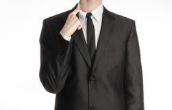 Επιχειρηματίας και θέμα χειρονομίας: ένα άτομο σε ένα μαύρους κοστούμι και έναν δεσμό που κρατούν ένα χέρι στο περιλαίμιο πουκάμι Στοκ εικόνες με δικαίωμα ελεύθερης χρήσης