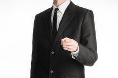 Επιχειρηματίας και θέμα χειρονομίας: ένα άτομο σε ένα μαύρο κοστούμι με έναν δεσμό παρουσιάζει χέρι του μπροστινό που απομονώνει  Στοκ Εικόνα