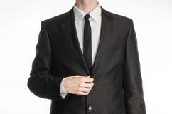 Επιχειρηματίας και θέμα χειρονομίας: ένα άτομο σε ένα μαύρο κοστούμι με ένα παλτό δεσμών ισιώνει τα όπλα του που απομονώνονται σε Στοκ εικόνες με δικαίωμα ελεύθερης χρήσης