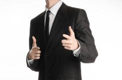 Επιχειρηματίας και θέμα χειρονομίας: ένα άτομο σε ένα μαύρο κοστούμι με έναν δεσμό που παρουσιάζει ένα σημάδι σε ετοιμότητα σας σ Στοκ φωτογραφία με δικαίωμα ελεύθερης χρήσης