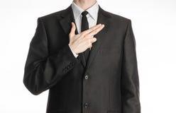 Επιχειρηματίας και θέμα χειρονομίας: ένα άτομο σε ένα μαύρο κοστούμι με έναν δεσμό έβαλε το χέρι του στο στήθος του με μια χειρον Στοκ Φωτογραφίες
