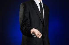 Επιχειρηματίας και θέμα χειρονομίας: ένα άτομο σε ένα μαύρο κοστούμι και το λευκό πουκάμισο κρατούν ψηλά ένα χέρι στο σκούρο μπλε Στοκ εικόνες με δικαίωμα ελεύθερης χρήσης