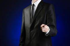 Επιχειρηματίας και θέμα χειρονομίας: ένα άτομο σε ένα μαύρο κοστούμι και ένα άσπρο πουκάμισο παρουσιάζει το χέρι ότι του προς τα  Στοκ Φωτογραφίες