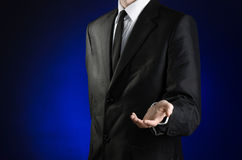 Επιχειρηματίας και θέμα χειρονομίας: ένα άτομο σε ένα μαύρο κοστούμι και το λευκό πουκάμισο κρατούν ψηλά ένα χέρι στο σκούρο μπλε Στοκ φωτογραφία με δικαίωμα ελεύθερης χρήσης