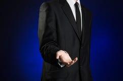 Επιχειρηματίας και θέμα χειρονομίας: ένα άτομο σε ένα μαύρο κοστούμι και το λευκό πουκάμισο κρατούν ψηλά ένα χέρι στο σκούρο μπλε Στοκ Φωτογραφία