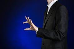 Επιχειρηματίας και θέμα χειρονομίας: ένα άτομο σε ένα μαύρο κοστούμι και ένα άσπρο πουκάμισο παρουσιάζει τσίμπημα χεριών σε ένα σ Στοκ Φωτογραφία