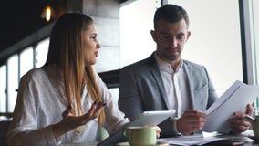 Επιχειρηματίας και μια επιχειρηματίας που χρησιμοποιούν τη σύγχρονη τεχνολογία ενώ διοργανώνοντας μια συνεδρίαση απόθεμα βίντεο