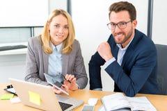 Επιχειρηματίας και ο βοηθός του που εργάζονται μαζί στο γραφείο Στοκ Φωτογραφίες