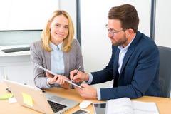 Επιχειρηματίας και ο βοηθός του που εργάζονται μαζί στο γραφείο Στοκ Φωτογραφία