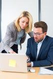 Επιχειρηματίας και ο βοηθός του που εργάζονται μαζί στο γραφείο Στοκ Εικόνες