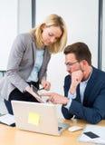 Επιχειρηματίας και ο βοηθός του που εργάζονται μαζί στο γραφείο Στοκ εικόνα με δικαίωμα ελεύθερης χρήσης