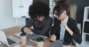 Επιχειρηματίας και επιχειρηματίας που εξετάζουν την έκθεση που χρησιμοποιεί την ψηφιακή ταμπλέτα στο γραφείο απόθεμα βίντεο