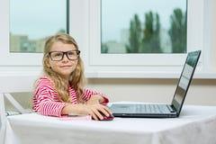 επιχειρηματίας λίγα Το κορίτσι παιδιών στα ενήλικα γυαλιά κάθεται στον πίνακα με τον υπολογιστή Στοκ φωτογραφίες με δικαίωμα ελεύθερης χρήσης