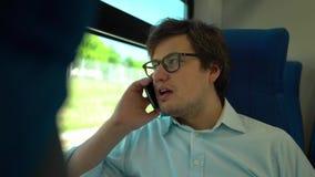 Επιχειρηματίας Μεσαίωνα στα γυαλιά που οδηγούν ένα τραίνο και που μιλούν στο τηλέφωνο απόθεμα βίντεο