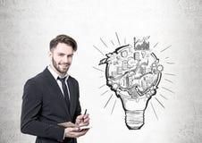 Επιχειρηματίας με έναν αρμόδιο για το σχεδιασμό, ένα σχέδιο lightbulb Στοκ φωτογραφίες με δικαίωμα ελεύθερης χρήσης