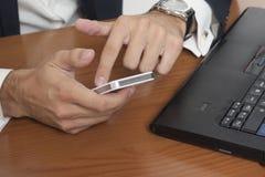 Επιχειρηματίας με ένα έξυπνα τηλέφωνο και ένα lap-top Στοκ Εικόνα
