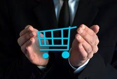 Επιχειρηματίας με ένα σύμβολο κάρρων αγορών Στοκ Εικόνες
