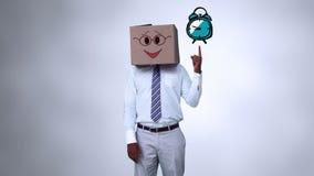 Επιχειρηματίας με ένα χαρτοκιβώτιο στο κεφάλι που δείχνει σε ένα ζωντανεψοντα ξυπνητήρι απόθεμα βίντεο