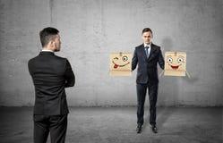 Επιχειρηματίας με γυρισμένη πίσω στο συγκεκριμένο υπόβαθρο που εξετάζει ένα άλλο άτομο που κρατά δύο κιβώτια με τα συρμένα πρόσωπ στοκ εικόνα