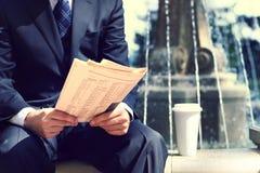 Επιχειρηματίας με μια εφημερίδα και έναν καφέ Στοκ Εικόνα