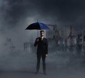 Επιχειρηματίας με μια ομπρέλα στις καταστροφές πόλεων Στοκ εικόνες με δικαίωμα ελεύθερης χρήσης
