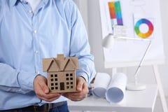 Επιχειρηματίας με μικροσκοπικό διαθέσιμο σπιτιών, στεμένος στην αρχή Στοκ φωτογραφία με δικαίωμα ελεύθερης χρήσης