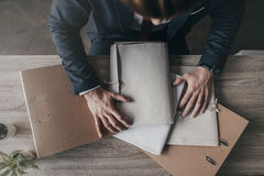 Επιχειρηματίας με τα έγγραφα και τους φακέλλους που κάθεται στον πίνακα στην αρχή Στοκ φωτογραφία με δικαίωμα ελεύθερης χρήσης