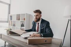 Επιχειρηματίας με τα έγγραφα και τους φακέλλους που κάθεται στον πίνακα στην αρχή Στοκ Εικόνες