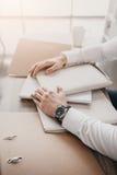 Επιχειρηματίας με τα έγγραφα και τους φακέλλους που κάθεται στον πίνακα στην αρχή Στοκ Φωτογραφίες