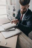Επιχειρηματίας με τα έγγραφα και τους φακέλλους που κοιτάζει στο ρολόι στην αρχή Στοκ εικόνες με δικαίωμα ελεύθερης χρήσης