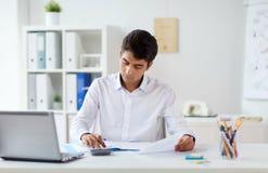 Επιχειρηματίας με τα έγγραφα και υπολογιστής στο γραφείο Στοκ φωτογραφίες με δικαίωμα ελεύθερης χρήσης