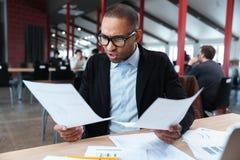 Επιχειρηματίας με τα έγγραφα και lap-top στο γραφείο Στοκ εικόνα με δικαίωμα ελεύθερης χρήσης