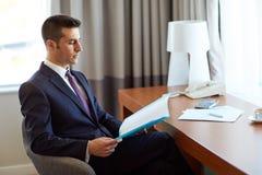 Επιχειρηματίας με τα έγγραφα που λειτουργούν στο δωμάτιο ξενοδοχείου Στοκ Φωτογραφία