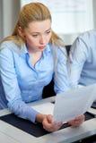 Επιχειρηματίας με τα έγγραφα που λειτουργούν στο γραφείο Στοκ Φωτογραφίες