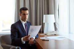 Επιχειρηματίας με τα έγγραφα που λειτουργούν στο δωμάτιο ξενοδοχείου Στοκ εικόνα με δικαίωμα ελεύθερης χρήσης