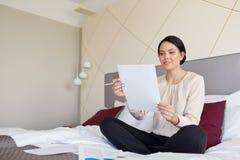 Επιχειρηματίας με τα έγγραφα που λειτουργούν στο δωμάτιο ξενοδοχείου Στοκ Εικόνα