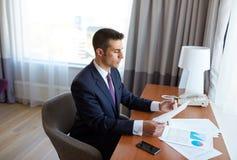 Επιχειρηματίας με τα έγγραφα που λειτουργούν στο δωμάτιο ξενοδοχείου Στοκ Εικόνες