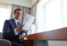 Επιχειρηματίας με τα έγγραφα που λειτουργούν στο δωμάτιο ξενοδοχείου Στοκ εικόνες με δικαίωμα ελεύθερης χρήσης