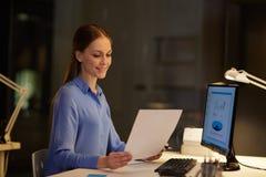 Επιχειρηματίας με τα έγγραφα που λειτουργούν τη νύχτα το γραφείο Στοκ εικόνα με δικαίωμα ελεύθερης χρήσης