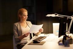 Επιχειρηματίας με τα έγγραφα που λειτουργούν τη νύχτα το γραφείο Στοκ φωτογραφία με δικαίωμα ελεύθερης χρήσης