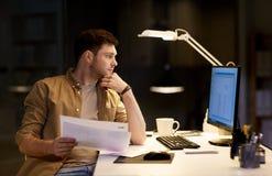 Επιχειρηματίας με τα έγγραφα που λειτουργούν τη νύχτα το γραφείο Στοκ Εικόνες