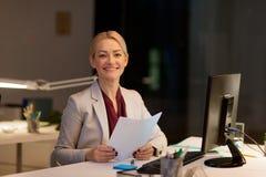 Επιχειρηματίας με τα έγγραφα που λειτουργούν τη νύχτα το γραφείο Στοκ εικόνες με δικαίωμα ελεύθερης χρήσης