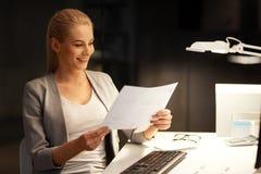Επιχειρηματίας με τα έγγραφα που λειτουργούν τη νύχτα το γραφείο Στοκ Εικόνα