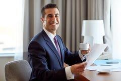 Επιχειρηματίας με τα έγγραφα που πίνει τον καφέ στο ξενοδοχείο Στοκ Εικόνες