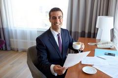 Επιχειρηματίας με τα έγγραφα που πίνει τον καφέ στο ξενοδοχείο Στοκ εικόνες με δικαίωμα ελεύθερης χρήσης